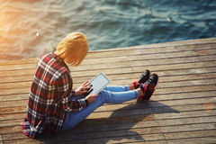 Young student is sitting on a pier near the ocean enjoying the beautiful weather and wrote its report Stock Photos