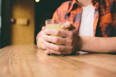 Young student is sitting in the restaurant and taste a warm drink. man drinking  tea at the cafe. Young student is sitting in the restaurant and taste a warm Royalty Free Stock Photo