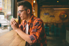 Young student is sitting in the restaurant and taste a warm drink. man drinking  tea at the cafe. Young student is sitting in the restaurant and taste a warm Stock Images