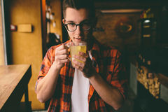 Young student is sitting in the restaurant and taste a warm drink. man drinking  tea at the cafe. Young student is sitting in the restaurant and taste a warm Stock Photos