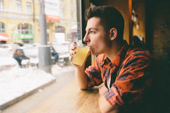 Young student is sitting in the restaurant and taste a warm drink. man drinking  tea at the cafe. Young student is sitting in the restaurant and taste a warm Stock Image