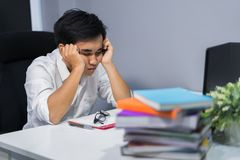 Young student sitting and sleeping at desk with book and laptop Royalty Free Stock Image