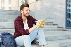 Young student making notes sitting on stairs. Young student sitting on stairs outdoors, making notes, preparing for exams at university or college. Education Stock Image