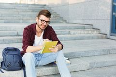 Young student making notes sitting on stairs. Young student sitting on stairs outdoors, making notes, preparing for exams at university or college. Education Royalty Free Stock Photography