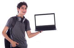 Young student smiling. Portrait of smiley happy friendly young student with hand in pocket holding a laptop, teenager wearing gray t-shirt with a headphone and Royalty Free Stock Image
