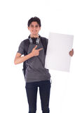 Young student smiling. Portrait of smiley happy friendly young student holding an empty blank board and pointing to it,  teenager wearing gray t-shirt and jeans Royalty Free Stock Photos