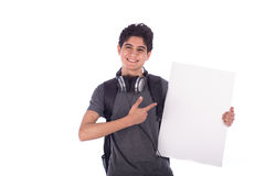 Young student smiling. Smiley happy friendly young student  holding an empty blank board and pointing to it,  teenager wearing gray t-shirt with a headphone and Stock Images