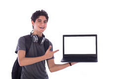 Young student smiling. Smiley happy friendly young student  holding a laptop and pointing to it, teenager wearing gray t-shirt with a headphone and back-bag Royalty Free Stock Image