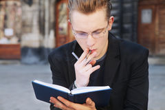 Young student smoking and preparing for the exam in old center o Stock Photography