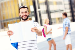 Young student standing in the campus with an open notebook Royalty Free Stock Images