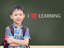 Young student standing in front of chalkboard Stock Image