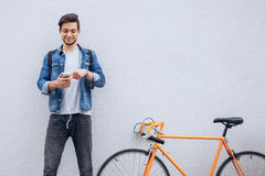 Young student standing near the bicycle looking at phone and listening to music. Young student in blue jeans jacket standing near the orange bicycle looking at Royalty Free Stock Photography
