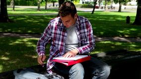 Young student studying on the bench outside Stock Photo