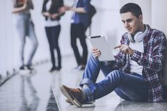 Young Student is a Studying in the Hall with Tablet. Young student is Studying in Hall with Tablet. Studying Young Man. Education and Career Concept. Studying royalty free stock image