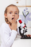 Young student surprised of what she saw on the microscope Royalty Free Stock Photography