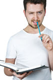 Young student taking notes. Young student winking and taking his notes on organizer wtih turquoise pen, the same color with his eyes Royalty Free Stock Images