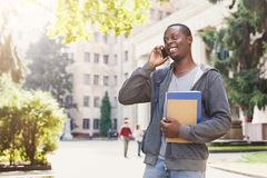 Young student talking on smartphone in the park. Young african-american student talking on smartphone, holding notebooks and backpack, standing at university Royalty Free Stock Photo
