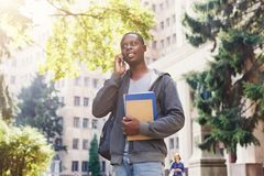 Young student talking on smartphone in the park. Young african-american student talking on smartphone, holding notebooks and backpack, standing at university Stock Photography