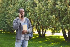 Young student talking on smartphone in the park. Young african-american student talking on smartphone, holding notebooks and backpack behind his shoulders in Royalty Free Stock Image