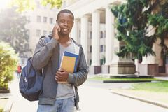 Young student talking on smartphone in the park. Young african-american student talking on smartphone, holding notebooks and backpack, standing at university Stock Photo