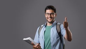 Young student with textbook. Portrait of young smiling student wearing eyeglasses with bristle holding white textbook, showing thumb up gesture and backpack on Stock Photography