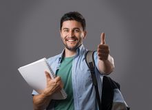 Young student with textbook. Portrait of young smiling student with bristle holding white textbook, showing thumb up gesture and backpack on his shoulder Royalty Free Stock Images