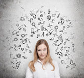 Young student is thinking about education at business school. Drawn business icons over the concrete wall. Stock Photo