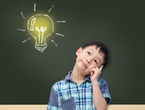 Young student thinking and looking up to light bulb. Young Asian student thinking and looking up to light bulb on chalkboard Royalty Free Stock Images