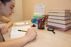 Young student with thoughtful expression sitting at a desk on some books. Education concept - little student girl with many books stock image
