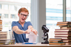 The young student tired and exhausted preparing for chemistry exam Stock Images