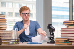 The young student tired and exhausted preparing for chemistry exam Stock Photo