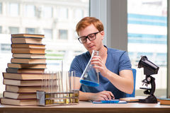 The young student tired and exhausted preparing for chemistry exam Stock Image