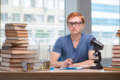 The young student tired and exhausted preparing for chemistry exam Stock Photography
