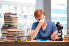 The young student tired and exhausted preparing for chemistry exam. Young student tired and exhausted preparing for chemistry exam Stock Image