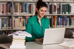 Young Student Using Her Laptop In A Library. In The Library - Pretty Female Student With Laptop And Books Working In A High School Or University Library Stock Images