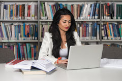 Young Student Using Her Laptop In A Library Royalty Free Stock Image