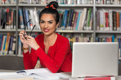 Young Student Using Her Laptop In A Library Royalty Free Stock Photography