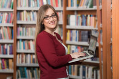 Young Student Using Her Laptop In A Library. In The Library - Pretty Female Student With Laptop And Books Working In A High School - University Library - Shallow Royalty Free Stock Photography