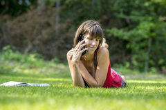 Young student using her mobile phone in the park lying on the gr Royalty Free Stock Images