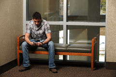 Young Student using his cell phone to text Royalty Free Stock Photo