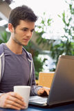 Young student using his laptop in cafe Stock Photo