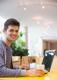 Young student using his laptop in cafe Stock Photos