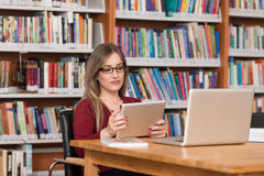 Young Student Using His Laptop In A Library. In The Library - Beautiful Female Student With Laptop And Books Working In A High School - University Library Stock Photography