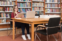 Young Student Using His Laptop In A Library. In The Library - Beautiful Female Student With Laptop And Books Working In A High School - University Library Royalty Free Stock Photography