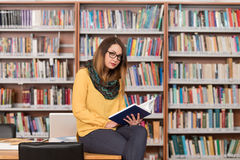 Young Student Using His Laptop In A Library. In The Library - Beautiful Female Student With Laptop And Books Working In A High School - University Library Royalty Free Stock Image