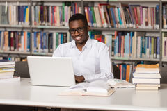 Young Student Using His Laptop In A Library Royalty Free Stock Images