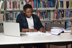 Young Student Using His Laptop In A Library Stock Photo