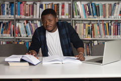 Young Student Using His Laptop In A Library Royalty Free Stock Photo
