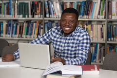 Young Student Using His Laptop In A Library Stock Image