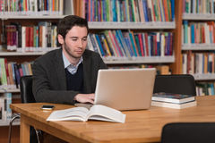 Young Student Using His Laptop In A Library. In The Library - Handsome Male Student With Laptop And Books Working In A High School - University Library - Shallow Stock Images